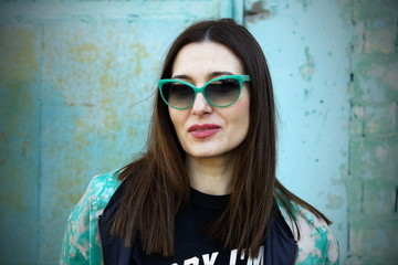 Closeup portrait of beautiful middle age white caucasian brunette woman in sunglasses on a green vintage background.