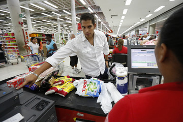A customer puts his finger on a fingerprint scanner as part of the process to buy groceries at Bicentenario, a state-run supermarket, in Caracas