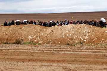 Syrian refugees walk with their families near Ruwaished