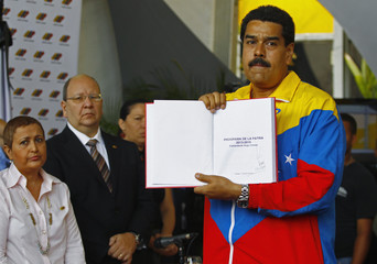 Venezuela's acting President, Maduro, shows the plan of government that was prepared by late President Chavez at the national election board in Caracas