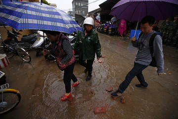 Villagers step on bricks as they walk towards a school to vote in an election for the next village chief and committee, on a flooded street in Wukan village