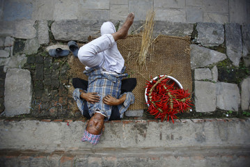 Man lies down outside his house after tying red chilli together, before drying them in the sun at Khokana, in Lalitpur