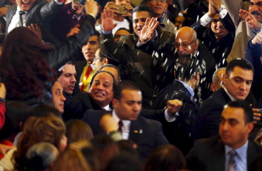 Egypt's President Abdel Fattah al-Sisi (C) receives flowers during Egypt's Coptic Christmas eve mass led by Pope Tawadros II in Cairo