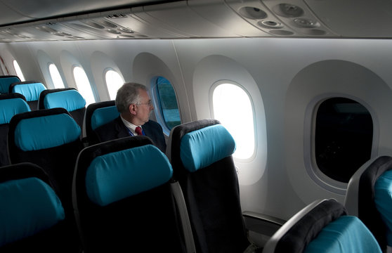 A Boeing employee sits next to a tinted window on the Boeing 787 Dreamliner at Farnborough airport in Farnborough, southern England