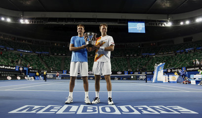 Lindstedt of Sweden and Kubot of Poland pose with the trophy after winning their men's doubles final match against Butorac of the U.S. and Klaasen of South Africa at the Australian Open 2014 tennis tournament in Melbourne