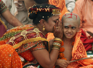 """A mother whispers sacred hymns in the ear of her son before he wears a """"janeyu"""" or sacred thread in Ahmedabad"""