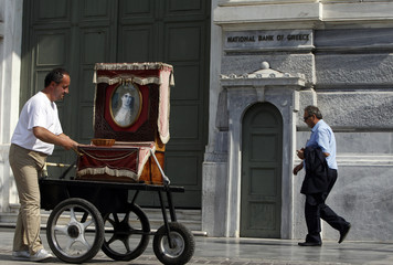 A man pushes a music box outside of the headquarters of the National bank of Greece in Athens