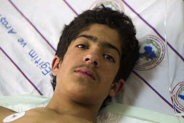 Tokay, 13-year old earthquake survivor, looks on as he rests at hospital after being rescued in eastern Turkish city of Van