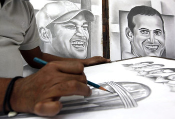 Hussain a street artist makes a pencil sketch of the Cricket World Cup trophy for sale at roadside in Kolkata