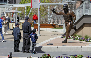 Fans look at a statue of former Minnesota Twins center fielder Kirby Puckett before the start of the Twins home opener in Minneapolis