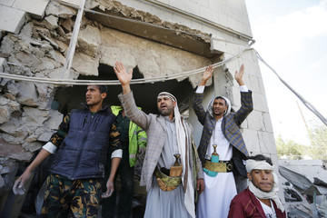 Rescuers gesture at the damaged residence of the Iranian ambassador after a car bomb attack in Sanaa