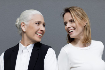Two beautiful women standing together and smiling each other isolated on grey