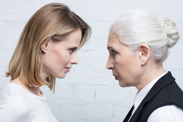 Side view of serious women looking at each other, young and senior people