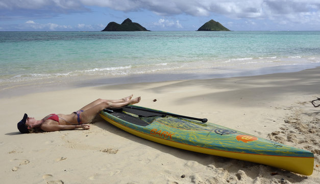 A woman rests her legs upon a kayak as she sunbathes on Lanikai Beach in Hawaii