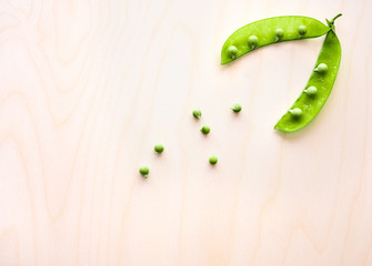 Pod of green peas and pea on a wooden surface, top view. Copy space
