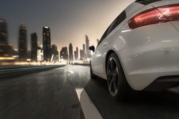 Auto fährt bei Abenddämmerung auf eine Stadt zu Fotomurales