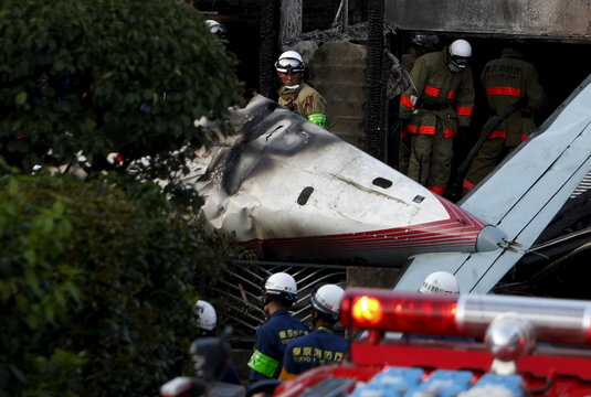 A firefighter looks at the tail section of a small airplane as he removes wreckage and debris at the site where the light plane went down in a residential area and burst into flames, in Chofu