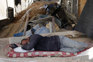 Palestinian tunnel worker sleeps at the entrance of a smuggling tunnel beneath the Gaza-Egypt border in the southern Gaza Strip
