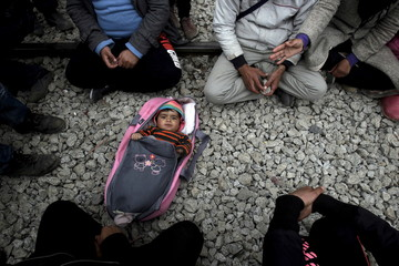 A baby is laid on the ground among stranded refugees and migrants waiting to cross the Greek-Macedonian border, near the Greek village of Idomeni