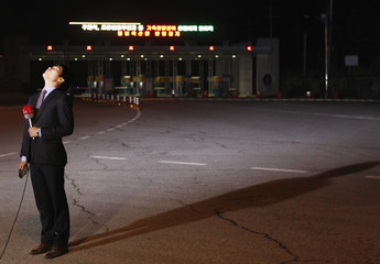 Local TV reporter prepares for news report in front of empty gate at CIQ office in Paju