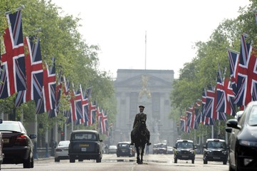 A soldier on horseback travels up The Mall with Buckingham Palace in the background