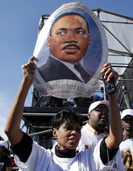 A woman holds a portrait of Martin Luther King, Jr. at a memorial dedication at the National Mall in Washington