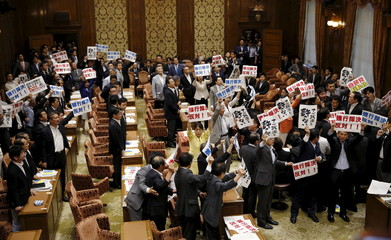 Hamada, chairman of the Lower House Special Committee on Security, is surrounded by opposition lawmakers during a vote on security-related legislation at the parliament in Tokyo