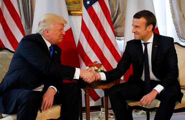 U.S. President Trump and French President Macron shake hands before a lunch ahead of a NATO Summit in Brussels