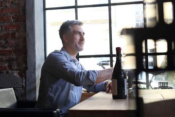 Randka w restauracji. Przystojny mężczyzna proponuje wino