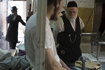 An Ultra-Orthodox Jewish man, the owner of a bakery, speaks to an employee during the preparation of matza in Bnei Brak