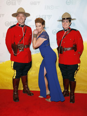 Canadian musician Edwards poses on the red carpet with a members of the Royal Canadian Mounted Police during the Juno Awards in Regina.