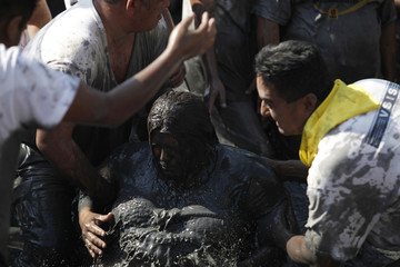 A penitent is baptised by a medium in a puddle of mud during celebrations for El Nino Fidencio in the town of Espinazo