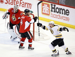 The Boston Bruins Tyler Seguin celebrates after teammate Dennis Seidenberg (not pictured) scored the game winning goal as the Senators Chris Phillips  and goaltender Robin Lehner skate away during the third period of their NHL hockey game at Scotiabank Pla