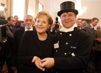 German Chancellor Merkel smiles after she received a coin from chimney sweeper Mussner at the President's annual New Year's reception in Berlin