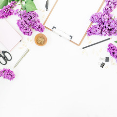 Freelance or blogger desk workspace with clipboard, notebook, scissors, lilac flowers and accessories on white background. Flat lay, top view