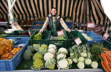 A market seller poses behind a fruit and vegetable stall in Detmold in the west German state of North Rhine Westphalia