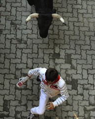 RA runner sprints in front of a Dolores Aguirre Ybarra fighting bull at the entrance to the bull ring during the second running of the bulls of the San Fermin festival in Pamplona