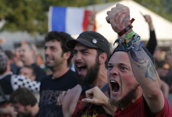 France soccer team fans react after their team scored a goal against Switzerland during their 2014 World Cup Group E soccer match, as they watch a live telecast of the match on a giant screen at the Hellfest music festival in Clisson