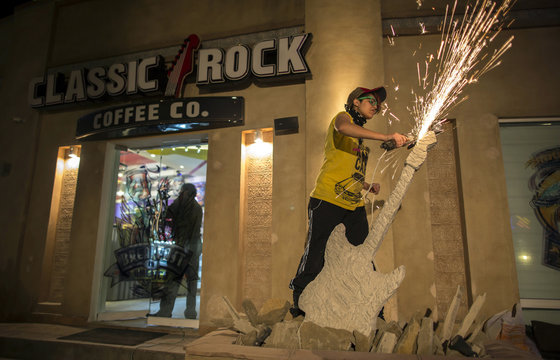 Interior designer Zahra Afridi uses a circular saw as she sculpts a stone guitar outside the Classic Rock Coffee cafe in Islamabad
