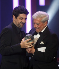 Director Gay receives the Best Original Screenplay trophy from writer Vargas Llosa during the Spanish Film Academy's Goya Awards ceremony in Madrid