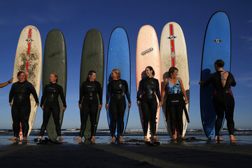 Women pose for a group photograph following a surf lesson at the beach in Rye