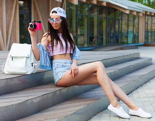 Leggy young cheerful hipster woman sitting on the steps in city wearing vintage pink top, jeans shorts and American flag sunglasses. Takes a picture of a pink vintage camera. Bag pack. Patriot. USA.