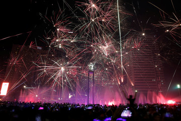 People watch fireworks explode around the Selamat Datang Monument during New Year's Eve celebrations in Jakarta