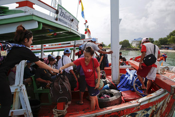 Tourists are assisted onto a boat as they leave Koh Samet island