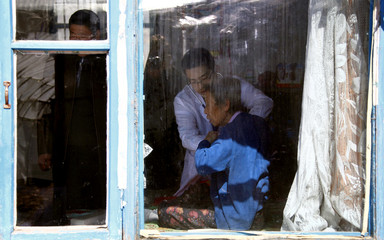 Doctor Li gives an old woman a check-up in her home as relatives look on in the village of Jianhua, located on the outskirts of the northern Chinese city of Shuangcheng in Heilongjiang province
