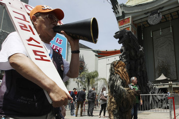 A street preacher and a person dressed as the Star Wars character Chewbacca stand near a statue of movie monster Godzilla in Los Angeles, California