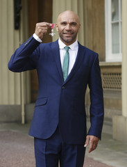 Musician and DJ Goldie holds his MBE award after it was presented to him by Prince Charles at Buckingham Palace in London