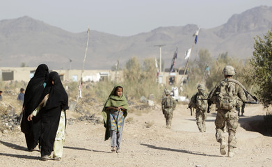 Residents walk past U.S. Army soldiers on a patrol in Zharay district in Kandahar province