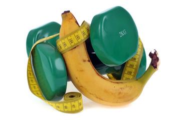 Banane avec des haltères et un mètre souple de couturière