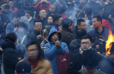People pray for good fortune as they hold burning incense at Yonghegong Lama Temple in Beijing